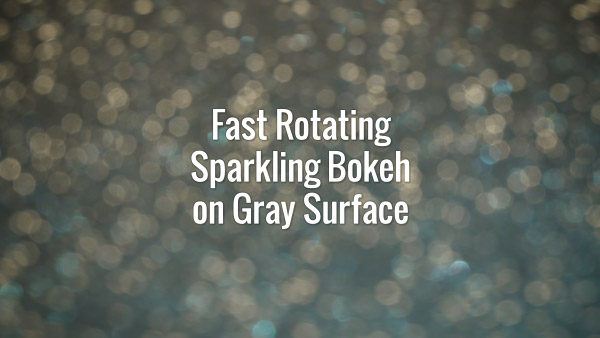 Seamlessly looping spinning flickering light yellow bokeh particles on gray surface.