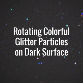 Seamlessly looping spinning flickering multicolored glitter particles on dark surface.