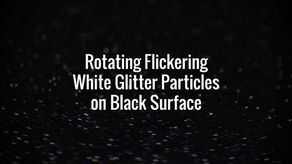 Seamlessly looping spinning light glitter particles on dark surface.