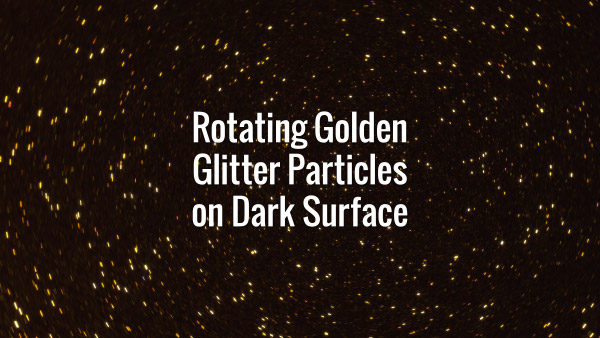 Seamlessly looping spinning flickering golden glitter particles on black surface.