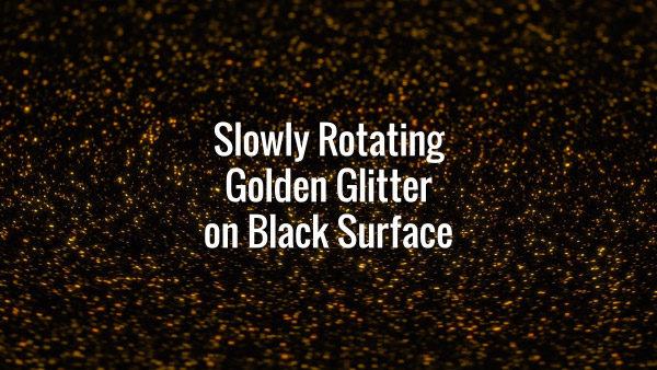 Seamlessly looping slowly rotating golden glitter particles on dark floor.