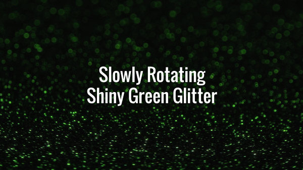 Seamlessly looping slowly spinning shiny green glitter particles on dark surface.