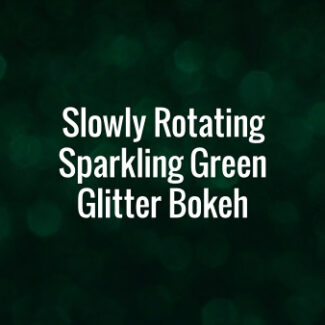 Seamlessly looping slowly spinning flickering green glitter bokeh particles on dark surface.
