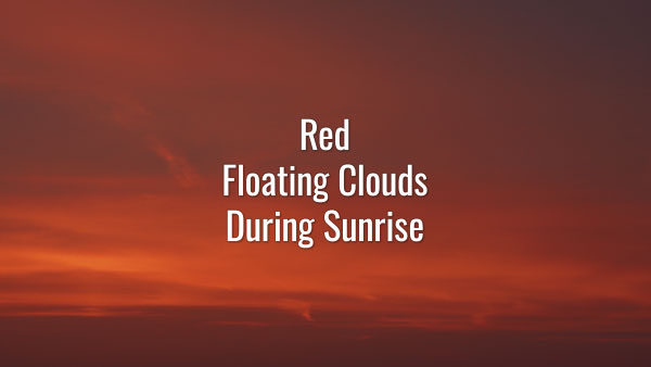 Time-lapse video of slowly floating peculiar orange and red clouds getting brighter during the sunrise