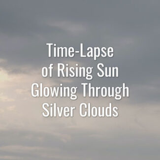 Time-lapse video of rising sun seeing through fast-moving gray clouds
